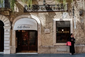 Woman takes break in front of historical coffee house Caffe Greco in downtown Rome.