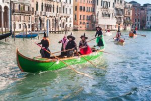 Celebrations of the Epiphany in Venice with locals dressed like Befana in a costumed regatta on the Grand Canal.