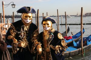 Carnevale in Venice with historical costumes and gondolas on the Grand Canal.