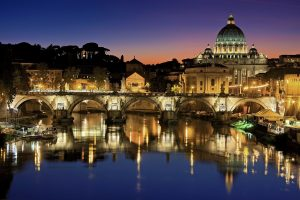 Stunning skyline of Rome at night with Basilica of St. Peter's Dome and Ponte SantAngelo Bridge over the Tiber River.