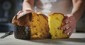 Baker opens a panettone cake from Milan, a popular Christmas cake in Italy.
