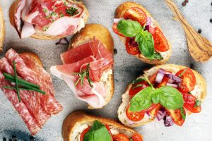 Small bruschetta from Italy made with prosciutto, salami and tomatoes on toasted bread and served with wine or cocktails at the aperitivo.