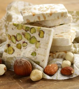 Torrone is a nougat desert popular across Italy at Christmas time. It is made from egg whites, honey and nuts.