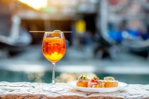 Spritz cocktail made with Aperol and Prosecco in Venice, Italy with cicchetti appertizers.