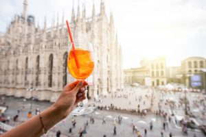 Toast with an Aperol Spritz cocktail on terrace in front of the Cathedral of Milan in Piazza del Duomo.